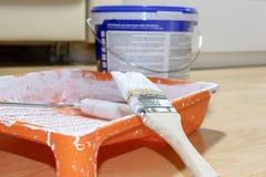 Bürste und Rolle in benutzter orange Farbwanne, Farbe können auf Hintergrund Wohnungsreparatur-, -malerei- und -konzept des Entwu stockbild