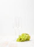 Bürste von grünen Trauben und von Gläsern auf Weiß Lizenzfreie Stockbilder