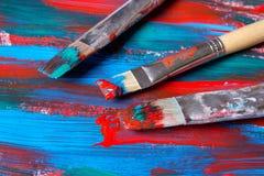 Bürsten auf Acrylfarbenhintergrund mit den blauen und roten Anschlägen Stockbild