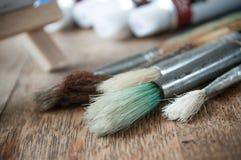 Bürsten für Acrylfarbe auf Holztischhintergrund Stockfotos