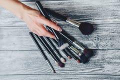 Bürsten für Make-up in den Händen auf hölzernem Hintergrund stockfoto