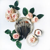 Bürsten Sie Ausrüstung, rosa Rosen, Weinlesebehälter und Retro- Platte auf weißem Hintergrund Stockbilder