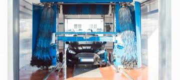 Bürsten Sie das Drehen in Waschanlage mit Fahrzeug in ihm lizenzfreies stockfoto