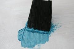 Bürsten Sie mit den Borsten, welche die Holzoberfläche mit blauer Farbe umfassen Lizenzfreie Stockbilder