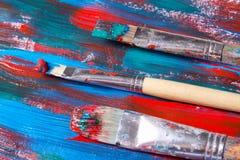 Bürsten und Acrylfarbenhintergrund mit den blauen und roten Anschlägen Lizenzfreie Stockfotografie