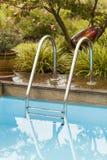 Bürsten-und Blatt-Abstreicheisen neben Swimmingpool Lizenzfreie Stockfotos