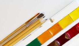 Bürsten und Bleistifte nahe bei Aquarellen auf Draufsichtkopienraum des Weißbuches lizenzfreie stockbilder