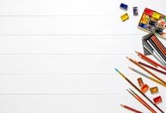 Bürsten und Farben mit Bleistiften auf hölzernem Hintergrund Stockfoto