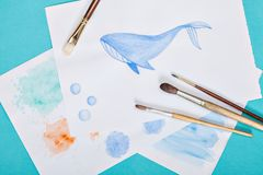 Bürsten und Zeichnung mit einem Wal auf dem Farbhintergrund Stockfotografie