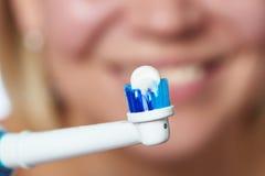 Bürstende elektrische Zahnbürste der Zähne der Frau mit Zahnpastamakro Stockbilder