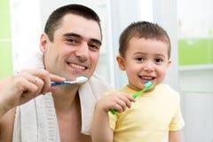 Bürstende schlafen gehende Zähne des Vater- und Kinderjungen Stockbild