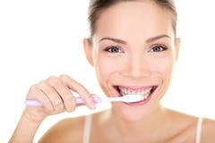 Bürstende Zähne der Frau, die Zahnbürste halten Stockfotos