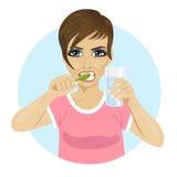 Bürstende Zähne der jungen Frau und halten Glas Wasser stock abbildung