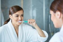 Bürstende Zähne der jungen hübschen Frau Stockbilder