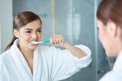 Bürstende Zähne der jungen hübschen Frau Stockbild