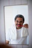 Bürstende Zähne des älteren Mannes im Badezimmer lizenzfreie stockfotografie