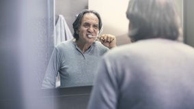 Bürstende Zähne des alten Mannes vor dem Spiegel stockfotografie