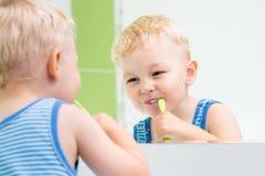 Bürstende Zähne des Kinderjungen im Badezimmer Stockbilder