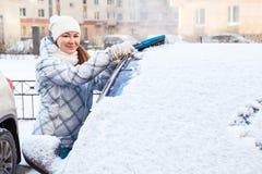 Bürstender Schnee der attraktiven Frau von der Autowindschutzscheibe Stockfotos