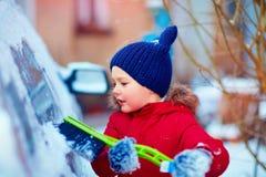 Bürstendes Auto des Jungen bedeckt mit Schnee Lizenzfreies Stockfoto