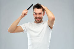 Bürstendes Haar des glücklichen Mannes mit Kamm über Grau Lizenzfreies Stockbild