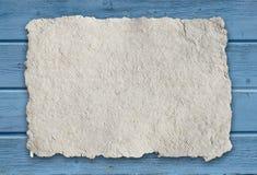 Büttenpapier mit Streifenmuster auf blauem hölzernem Hintergrund Stockfotografie