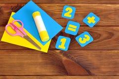 Büttenpapierkarten mit Zahlen, Scheren, Papierblätter, Kleber auf einem braunen hölzernen Hintergrund getrennte alte Bücher Lizenzfreies Stockbild