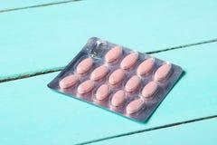 Bąbel różowe pigułki na błękitnym drewnianym tle obrazy royalty free