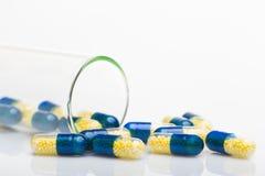 Błękit żółte kapsuły na białym stole Zdjęcia Royalty Free