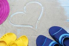 Błękit, żółte trzepnięcie klapy i serce na piaskowatej plaży, Zdjęcia Stock