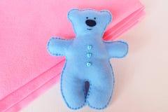 Błękit filc niedźwiedź na bielu i menchii tle, zaszyta zabawka Zdjęcia Royalty Free
