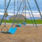 Błękit huśtawka z domami góra i niebo widokiem zdjęcia stock