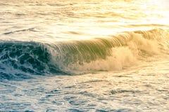 Błękit i żółta wiruje morze fala zalewamy brzeg przy zmierzchem fotografia stock