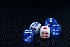 Błękit i biel dices na glansowanym czarnym tle Fotografia Stock