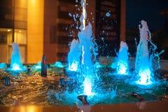 Błękit iluminować fontanny w nocy mieście zdjęcie stock