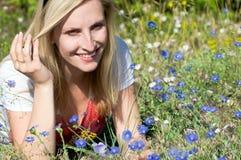 błękit kwitnie przyglądającej kobiety Zdjęcie Royalty Free