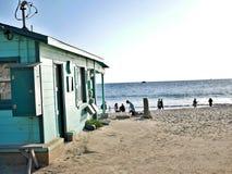 Błękit plażowa chałupa na Kalifornia oceanie z ludźmi chodzi i bawić się na brzeg Fotografia Stock