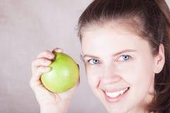 Błękit przyglądał się młodej kobiety ono uśmiecha się z zielonym jabłkiem w ręce Zdjęcia Stock
