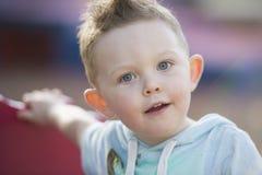 Błękit przyglądająca się chłopiec pauzuje podczas gdy bawić się przy parkiem w Australia zdjęcia royalty free