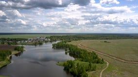 Błękit spokojna rzeka odbija białe chmury blisko małej wioski zdjęcie wideo