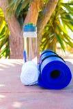 Błękit Staczająca się joga maty butelka z Wodnym Białym ręcznikiem na Greenery drzewka palmowego natury tle sunlight Relaksu lata zdjęcie stock