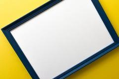 Błękita obrazka pusta rama na kolor żółty ściany tle Obrazy Royalty Free
