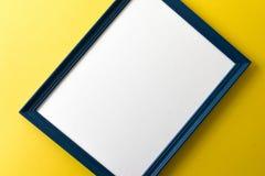 Błękita obrazka pusta rama na kolor żółty ściany tle Zdjęcia Royalty Free