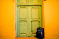 Błękita plecy - pakuje blisko zielonej drzwi i koloru żółtego ściany Zdjęcie Royalty Free