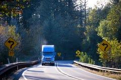 Błękita semi ciężarówka na pogodnej cewienie zieleni drodze z drzewami obrazy royalty free
