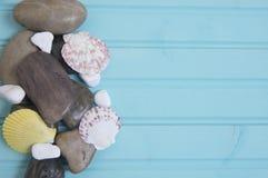 Błękita tła plażowy wizerunek otoczaki i wielo- colour skorupy lekcy i ciemni Zdjęcie Stock