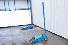 Błękitna dźwigarka dla podnosić samochodów stojaki na asfalcie Wyposażenie dla zmieniać koła zdjęcia stock