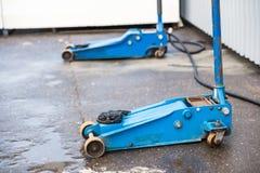 Błękitna dźwigarka dla podnosić samochodów stojaki na asfalcie Wyposażenie dla zmieniać koła zdjęcie stock