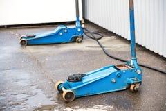 Błękitna dźwigarka dla podnosić samochodów stojaki na asfalcie Wyposażenie dla zmieniać koła obraz stock