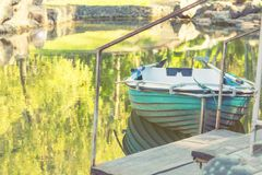Błękitna drewniana łódź w parkowym stawie na słonecznym dniu Zdjęcia Royalty Free